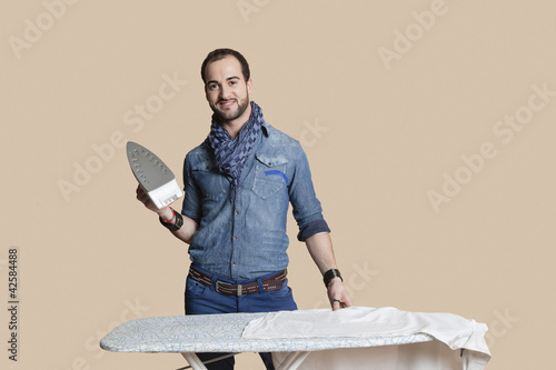 Portrait of a young man holding iron over colored background