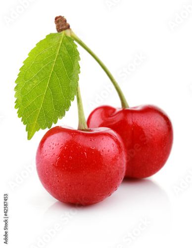 Ripe cherry berries with green leaf isolated on white
