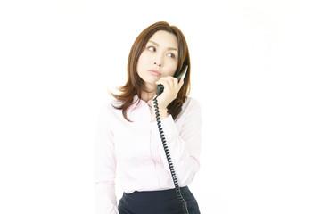 受話器を持っているオフィスレディー