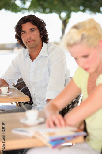 Two people drinking coffee on a terrace