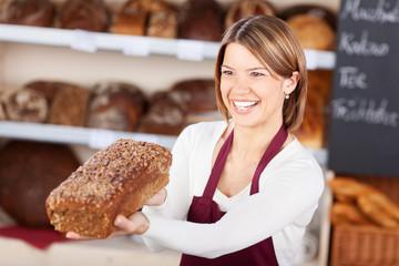 lächelnde verkäuferin mit vollkornbrot