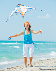 Woman on beach playing with a colorful kite