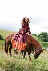 beautiful gypsy girl in a red dress. He sits on the horse