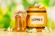 Sweet honey in barrel and jar with flowers
