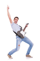 young casual man playing an electric guitar