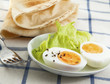 Hard boiled egg with salad on the textile background