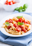 Penne with cherry tomatoes and basil on kitchen table
