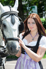 Woman in dirndl with horse