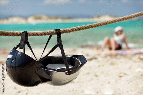 Helmets on the beach. Young woman relaxing on the background.