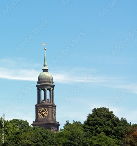 Church tower behind a forest