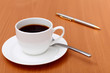 Black coffee in a cup and pen