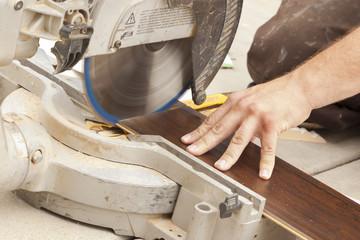 Contractor Using Circular Saw Cutting of New Laminate Flooring
