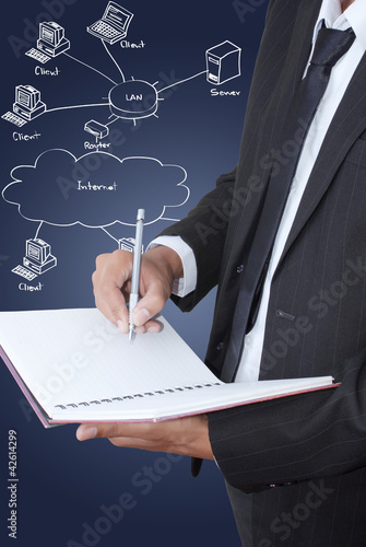 Businessman write on notebook with LAN diagram.