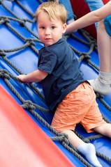 Kleiner Junge am Kletterseil