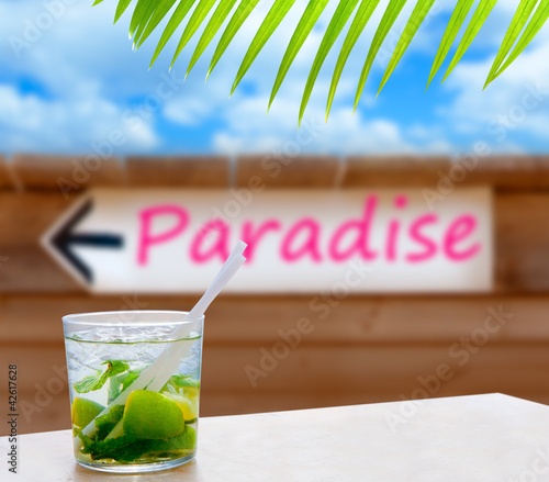 Cocktail mojito in a written paradise word arrow sign