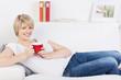 entspannte frau mit tasse auf dem sofa
