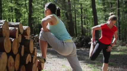 Two young women exercising and stretching in the forest, steadyc