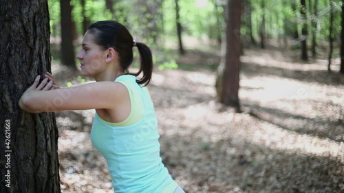 Young woman exercising in the forest, dolly shot