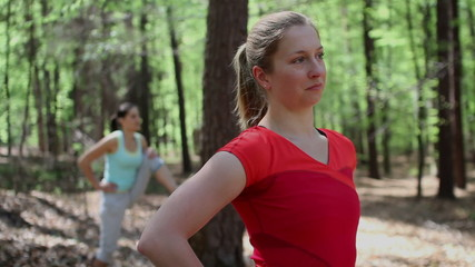 Portrait of happy woman exercising with friend in the forest, st