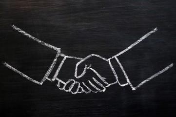 Chalk drawing of handshaking on a blackboard