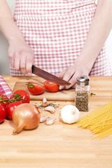 nahaufnahme beim schneiden von tomaten für spaghetti
