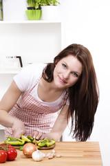junge frau in der küche schneidet grüne paprika