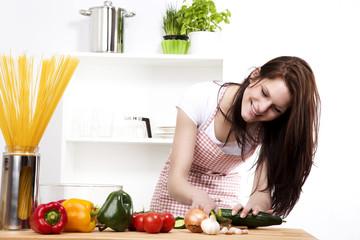 junge fröhliche frau beim zubereiten von gemüsesalat