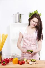 junge lachende frau in der küche beim zubereiten von salat
