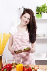 junge lachende frau in der küche bereitet salat zu