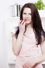 hübsche frau in der küche isst paprika