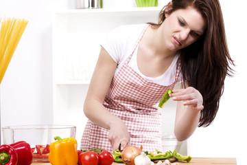 hübsche frau in der küche schaut angewidert ein stück paprika an