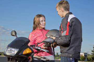 The guy gives to the girl a helmet