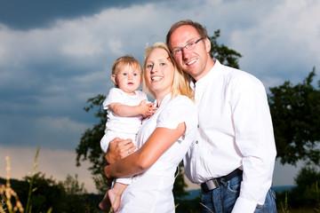 Glückliche Familie mit Baby auf Wiese