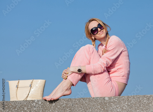 Girl in sunglasses with bag on background of sky