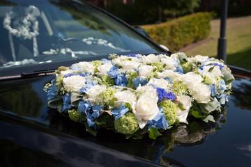 Hochzeitsblumenstrauß auf Motorhaube in der Sonne