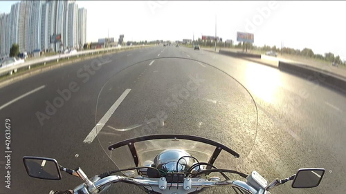 Biker driving the motorcycle on city highway, POV
