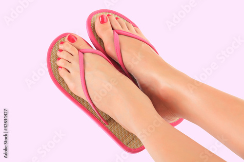 female legs in pink sandals on pink background
