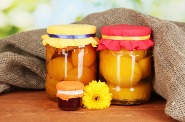 Jars with canned fruit on wooden background