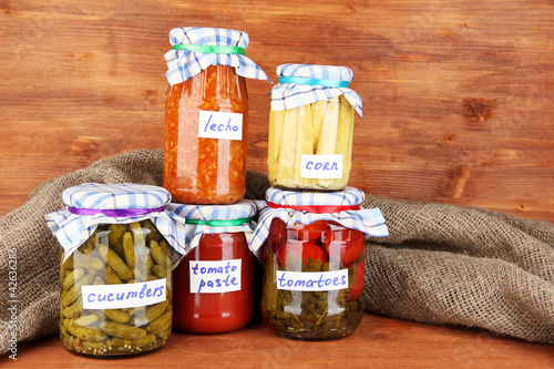 Jars with canned vegetables on green background close-up