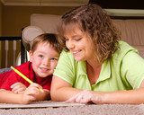 Mother helping child with writing lesson for school