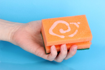 Sponge in hand with detergent on blue background