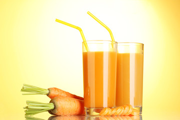 glasses of carrot juice on yellow background