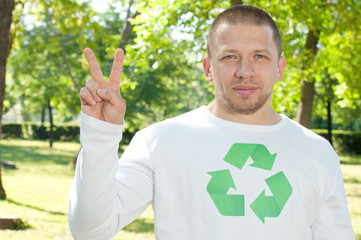A positive man with recycle logo on his shirt showing V-sign