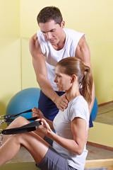 Trainer korrigiert Körperhaltung bei Frau