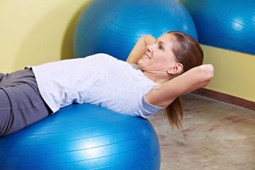 Frau trainiert auf Gymnastikball