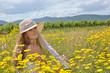 Sommer-Glück: Junge Frau mit Strohhut auf Blumenwiese