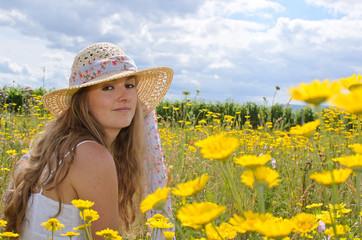 Sommer-Glück: Mädchen mit Strohhut auf Blumenwiese