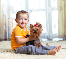 kid hugging puppy indoor