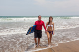 Happy man and the girl go together on an ocean coast