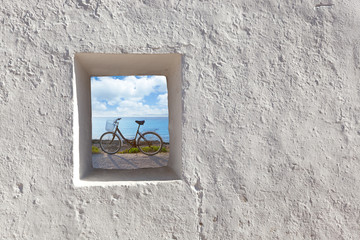 Balearic islands beach and bicycle through window